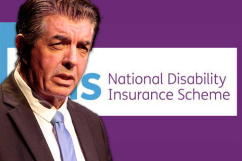 Minister Williams in front of NDIS logo