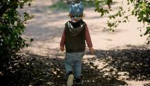 child walking away in tree shadow
