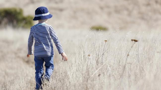 child walking away in long dry grass