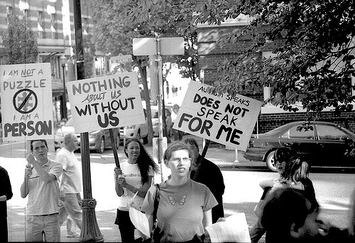 """people holding """"nothing about us without us"""" placards"""
