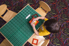child seated at a learning table
