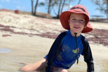 Mitchell Fielke is non-verbal but loves tactile surfaces such as the water and sand. (Supplied: Catherine Fielke)