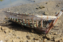 derelict boat on sand at low tide